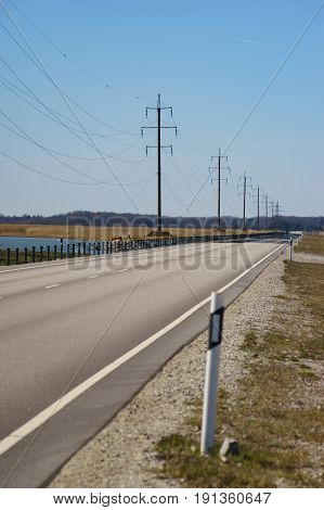 Straight road and high-voltage power transmission line against blue sky. Diminishing perspective vertical composition