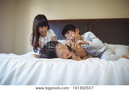 Happy family relaxing on bed in the bed room at home
