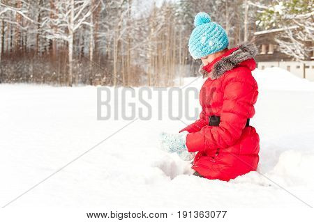 Playful winter. Young cheerful teenage girl sitting in snowdrift enjoying winter weather. Bright outdoors horizontal image.