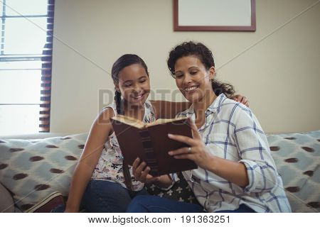 Mother and daughter reading book in living room at home