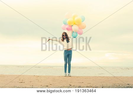 The summer is over. Cheerful young girl with colored balloons on the beach. Outdoors with instagram filter.