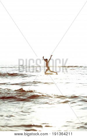 Running through the waves. Silhouette of happy girl having fun and jumping in the sea in rays of sunlight with raised up arms. Vertical summertime outdoors image.