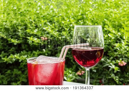 A glass of tinto de verano, a Spanish summer cocktail, and a glass of red wine, on a terrace in a garden, with a place for text. Selective focus