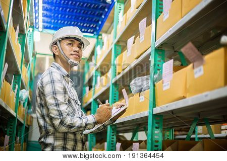 Asian man check agricultural equipment stock with smile