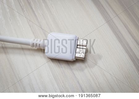 White usb 3.0 cable with micro B connector on woodbackground close up image