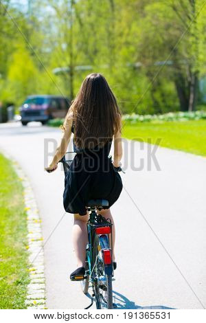 Back view of girl on bicycle wearing on black short dress. Young Woman riding along road on green spring  Park. Sporty young girl riding a bicycle on a sunny morning, view from the back