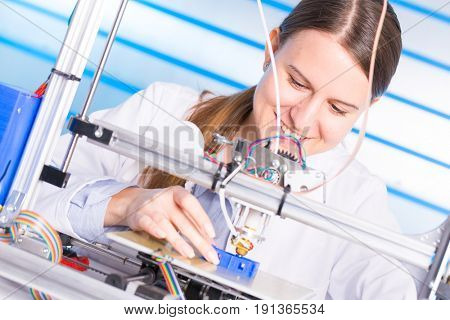A female student or laboratory assistant in the automation laboratory is debugging the work of the 3d printer. 3d printer is a device for modeling objects