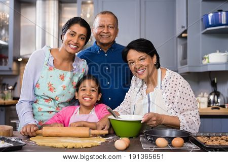 Portrait of multi-generation family standing together in kitchen at home