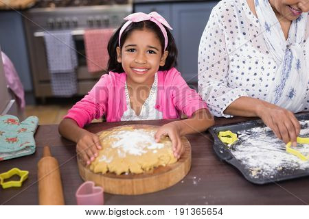 Portrait of smiling girl preparing food in kitchen at home
