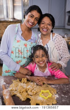 Portrait of smiling multi-generation family standing by dough in kitchen at home