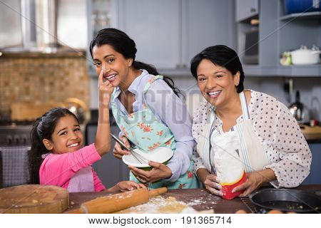 Portrait of cheerful multi-generation family preparing food together in kitchen at home