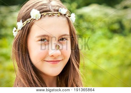 Portrait of Looking at camera boho style cheerful girl with floral headband on head and butterfly on nose. Summertime horizontal outdoors image