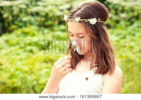 Happy boho style cheerful girl with floral headband on head and butterfly smelling camomile. Summertime multicolored outdoors horizontal image.