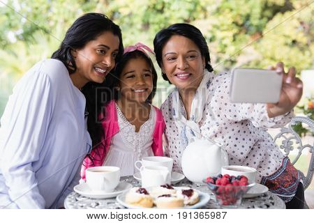 Smiling multi-generation family taking selfie while sitting together by breakfast table at home