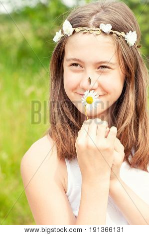 Happy boho style cheerful girl with floral headband on head and butterfly on nose smelling camomile. Summertime outdoors.