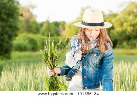 Happy cheerful young girl in summer hat collecting stems in rays of sunlight on wheat field. Multi colored summertime outdoors horizontal image.