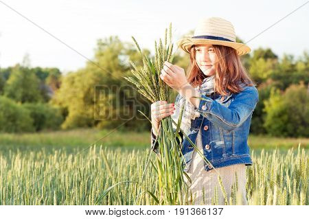 Happy young girl in summer hat collecting stems on wheat field. Summertime outdoors.
