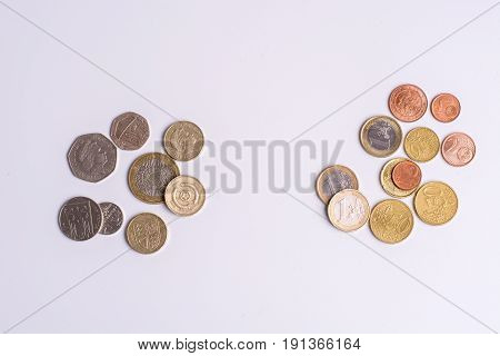 British Pound Coins And Euro Coins On White Background