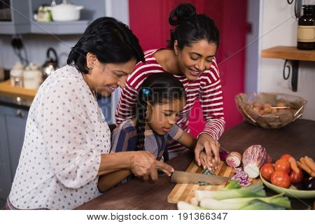 Multi-generation family preparing food together in kitchen at home