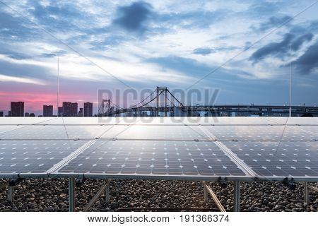 solar panel with modern suspension bridge in tokyo at twilight