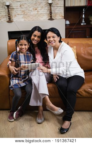 Portrait of smiling multi-generation family using digital tablet while sitting together on sofa at home