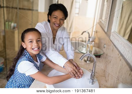 Portrait of grandmother and granddaughter washing hands at bathroom sink