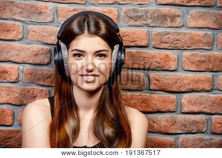 Happy young woman enjoys music in headphones. Brick wall background.