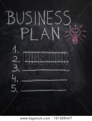Business plan list and red lightbulb written, drawn with chalk on blackboard
