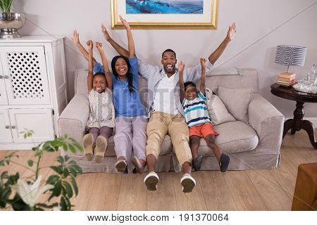Portrait of happy family cheering while sitting on sofa at home