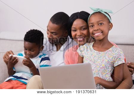Happy family with laptop and digital tablet sitting on sofa at home