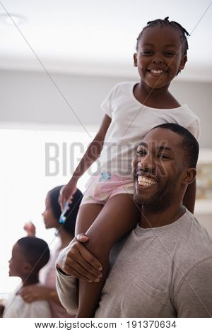 Portrait of happy father carrying carrying daughter in bathroom at home