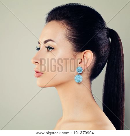 Beautiful Young Woman with Blue Earrings. Profile