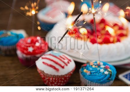 Patriotic 4th of july cake and cupcake arranged on wooden table