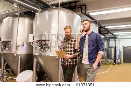 manufacture, business and people concept - men with clipboard working at craft brewery or beer plant and calling on smartphone