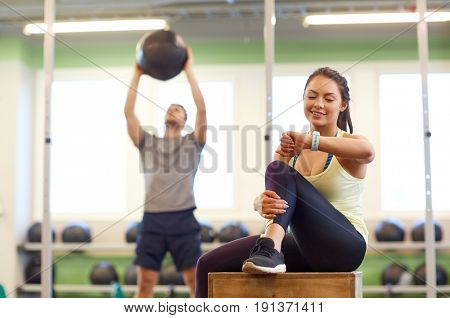 sport, training and people concept - man exercising with medicine ball and woman tracking time on fitness tracker in gym