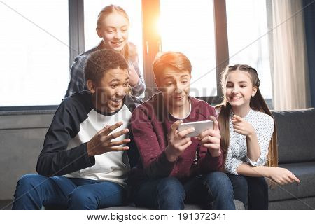 Happy Multicultural Teenagers Group Video Call With Smartphone And Sitting On Sofa At Home, Teenager