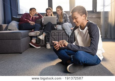 Smiling Teenage Boy Sitting On Floor And Using Smartphone With Friends Using Laptop Behind