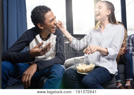 Happy teenage couple eating popcorn from glass bowl indoors teenagers having fun concept