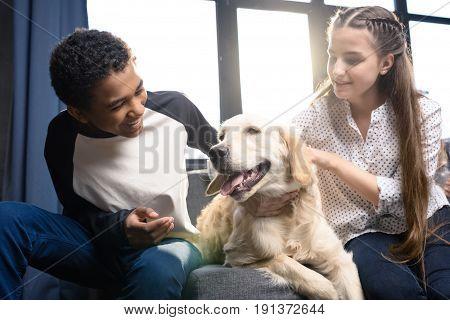 Happy teenage couple having fun with golden retriever dog indoors teenagers having fun concept