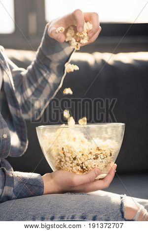 Close-up Partial View Of Person Eating Popcorn From Glass Bowl