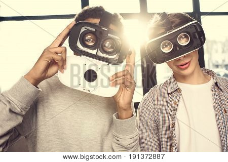 Two Teenagers In Virtual Reality Headsets Standing Together And Looking At Camera, Teenagers Having