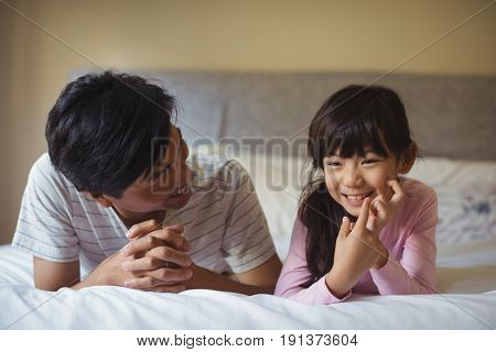 Father and daughter lying together in bedroom at home