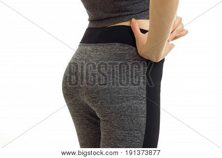 Sports supple buttocks of a young girl in trousers is isolated on a white background close-up