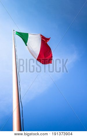 Waving Italian flag tricolor against blue sky