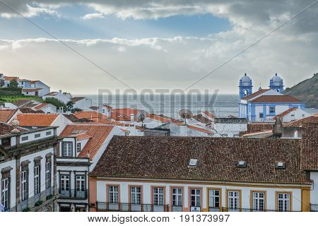 Wide view of church and roofs in Angra do Heroismo with atlantic ocean in the background, Island of Terceira in Azores, Portugal