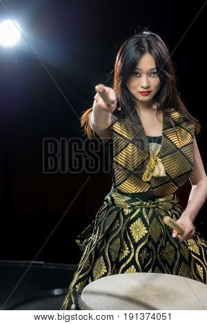beautiful asian long haired drummer girl with drumsticks, studio consetr shot on a dark background. soffit light and copy space at the side.