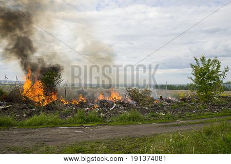 The fire at the dump in a suburban area on the background of the city