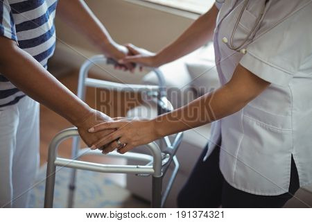 Mid section of female doctor helping senior woman to walk with walker at home