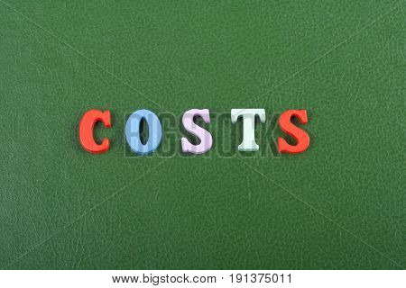costs word on green background composed from colorful abc alphabet block wooden letters, copy space for ad text. Learning english concept
