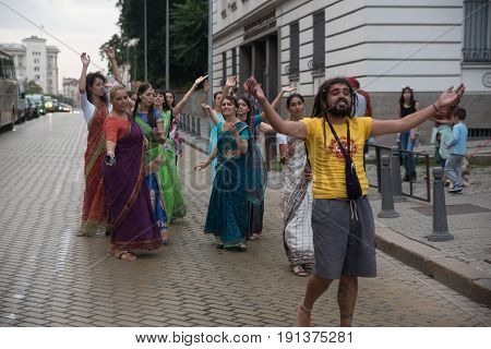 SofiaBulgaria - September 10 2016: The cart festival called 'Ratha Yatra' in Sofia september 10 2016. Priests throw fruits offered to the deities to the people lifting up their hands to catch.